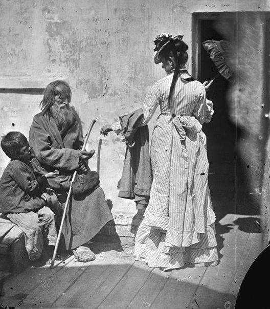На снимке: Дама подает милостыню нищим.