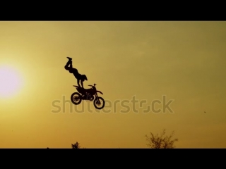 Stock-footage-slow-motion-silhouette-pro-motocross-rider-riding-fmx-motorbike-jumping-big-air-kicker-performing