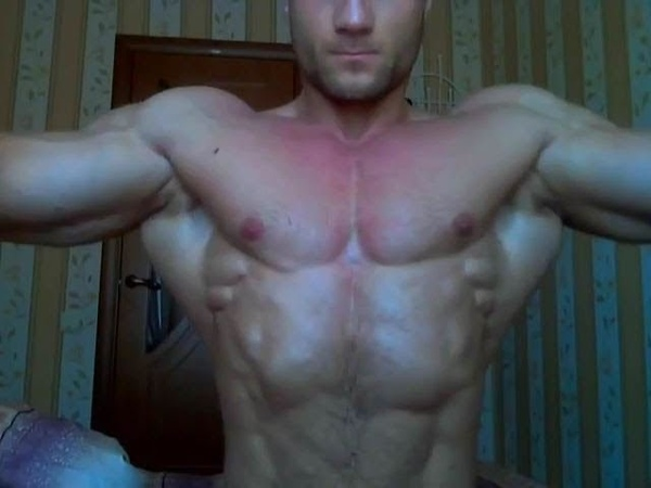 Massive athlete flexing and posing in bedroom