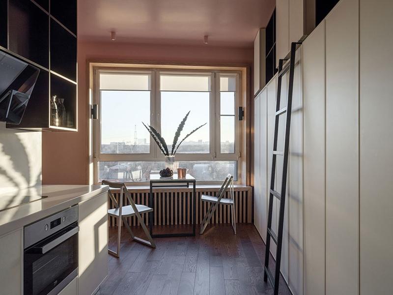 Интерьер квартиры-студии 29 м в Москве с разворотом кухни, спальной нишей и рабочими местами в шкафу.